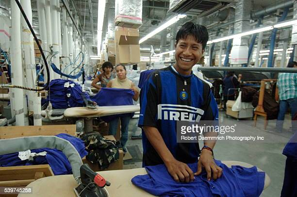 A worker laughs while ironing clothing at the BonWorth clothing factory in Mexico on March 24 2006 Clothing manufacturer BonWorth factory has 650...