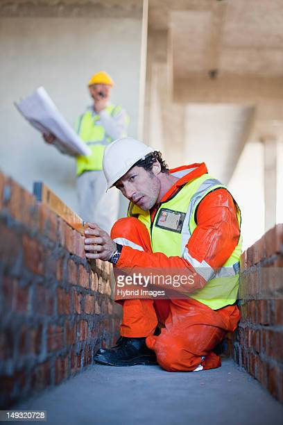 Worker laying brick at construction site
