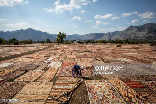 A worker lays carpets out to dry on August 10 2018 in Dosemealti Turkey Turkey is famous for its artisan carpets but before they are sent to stores...