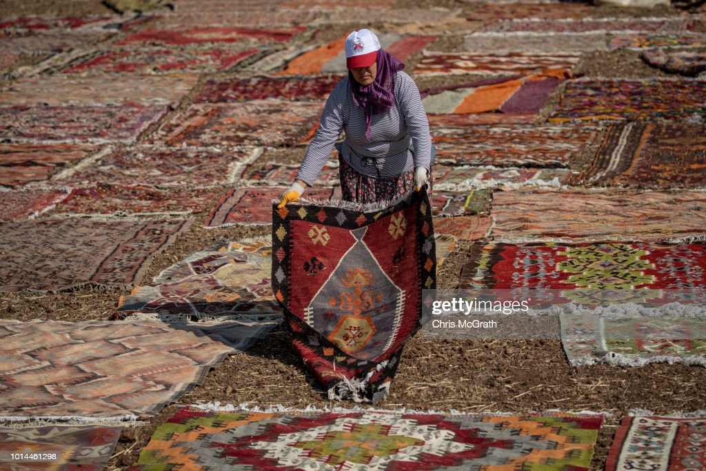 A worker lays carpets out to dry on August 10, 2018 in Dosemealti, Turkey. Turkey is famous for its artisan carpets but before they are sent to stores, masses of handmade carpets, flat woven kilims and embroidered rugs from all over Turkey are sent to the Dosemealti district in Antalya. The carpets are laid out in the sun and are turned regularly to soften the colors and give them an antique look. Turkey's carpet industry employs more than 40,000 people and exports have risen in the past five years to more than 10bn USD .