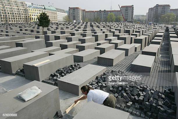Worker lays cobblestones among the approximately 2,700 concrete slabs, or stellae, at the Memorial to the Murdered Jews of Europe at the memorial's...