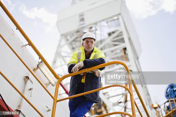 trabalhador inclinada no parapeito da plataforma petrolífera - capacete equipamento - fotografias e filmes do acervo
