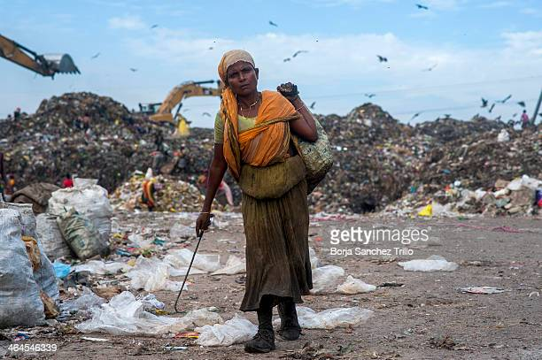 A worker leaves a landfill with items she has collected on November 17 2013 in Dhaka Bangladesh Bangladesh currently holds one of the lowest minimum...