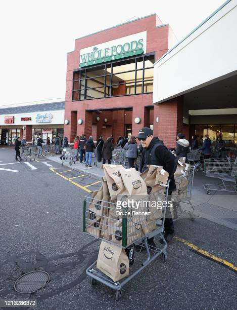 Worker leaves Whole Foods with Amazon Prime delivery packages on March 18, 2020 in Jericho, New York. The World Health Organization declared COVID-19...