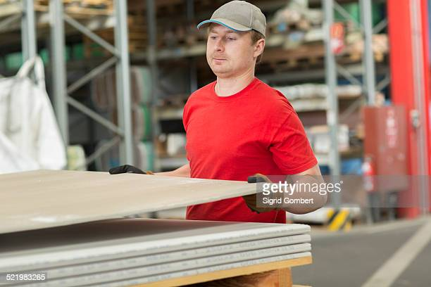 Worker lifting boards in hardware store warehouse