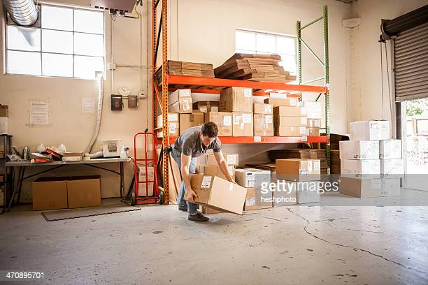 worker lifting cardboard box - heshphoto stock pictures, royalty-free photos & images