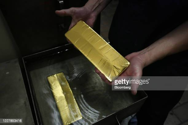 Worker lifts a gold ingot from a cooling bath at the Uralelectromed Copper Refinery, operated by Ural Mining and Metallurgical Co. , in Verkhnyaya...