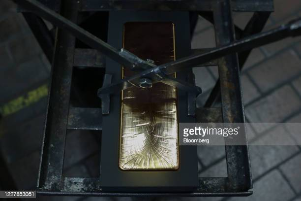 Worker lifts a gold ingot from its mold after cooling at the Uralelectromed Copper Refinery, operated by Ural Mining and Metallurgical Co. , in...