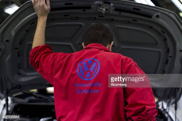 A worker lifts the hood to inspect the engine bay of a completed Volkswagen AG Caddy van during quality control checks at the end of the production...