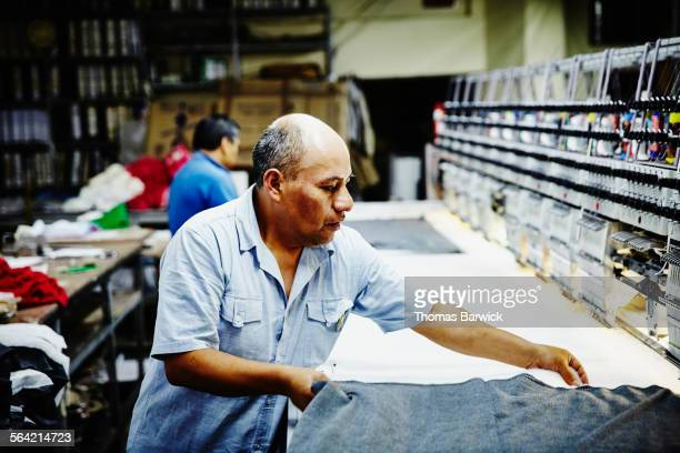 worker lining up fabric on embroidery machine - embroidery stock pictures, royalty-free photos & images