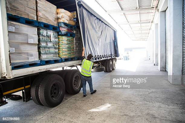 Worker loading a lorry at a large warehouse