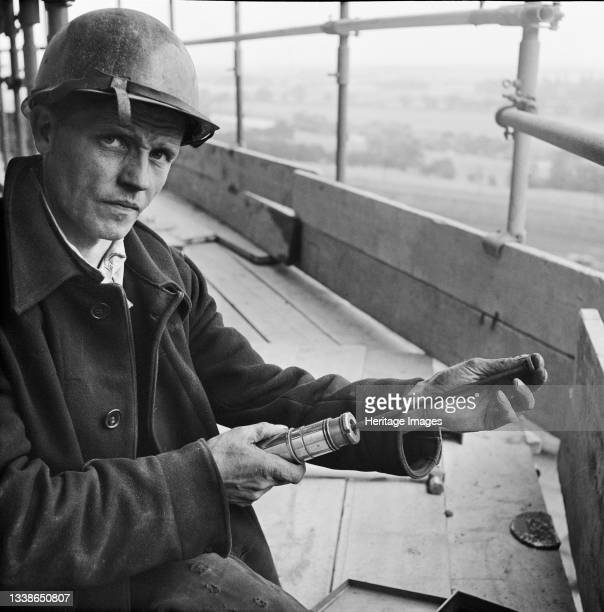 Worker loading a riveting gun during the construction of two sugar silos at Poppleton Sugar Beet Factory. Two sugar silos were built by Laing for the...