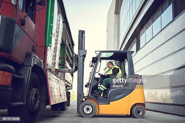 worker loading pallet with a forklift into a truck. - sollevare foto e immagini stock