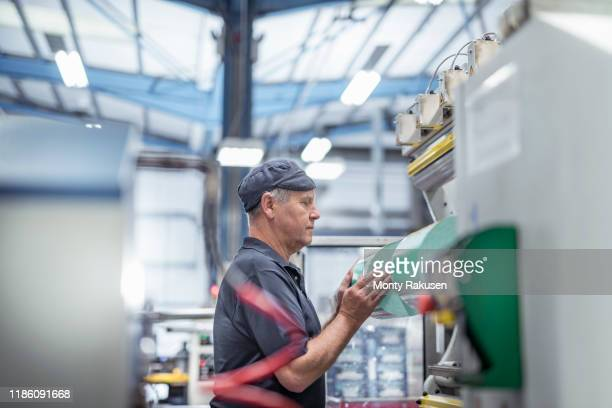 worker loading plastic packaging in print machine in print factory - packaging stock pictures, royalty-free photos & images