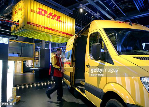 Worker loads a DHL package onto a delivery vehicle at the DHL Technology and Innovation Center in Troisdorf near Bonn, Germany, Tuesday, March 27,...