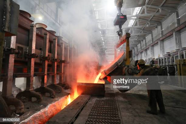 A worker loads a liquid electrolyte into the electrolysis bath inside the electrolysis shop at the Krasnoyarsk aluminum smelter operated by United Co...