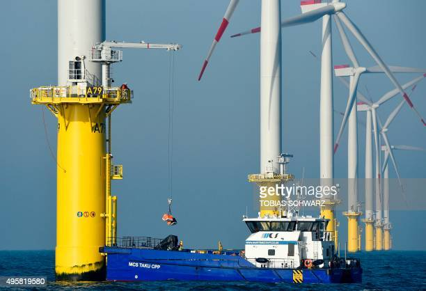 A worker loads a service vessel from a wind turbine run by Germany's biggest power supplier Eon at the offshore wind farm Amrumbank West near the...