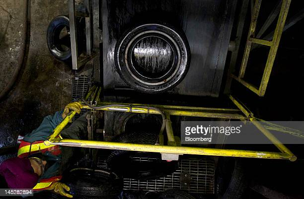 A worker loads a tire onto a conveyor belt at the Emterra Tire Recycling facility in Brampton Ontario Canada on Tuesday Nov 1 2011 Emterra Tire...