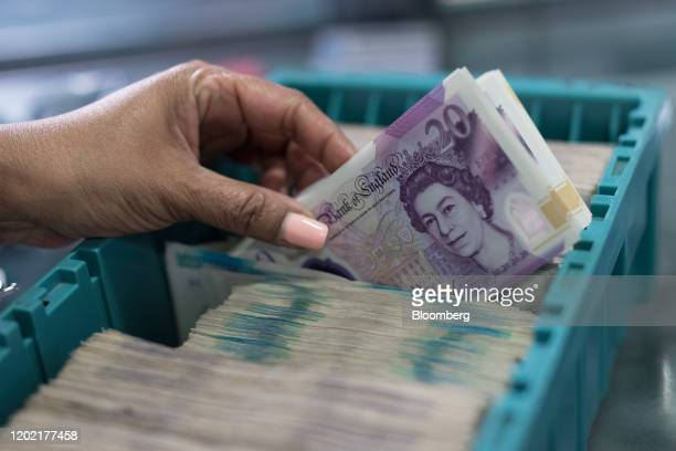 A worker loads a tray with bundles of British pound banknotes to feed into a note sorting machine in a warehouse operated by G4S Plc in London UK on...