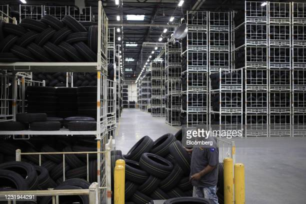 Worker loads automotive tires onto a conveyor belt at the Continental Tire distribution center in Sumter, South Carolina, U.S., on Tuesday, March 23,...