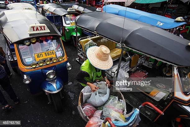 A worker loads bags of groceries onto a tuktuk at the Klong Thoei market in Bangkok Thailand on Friday Aug 15 2014 Thailands economy expanded in the...