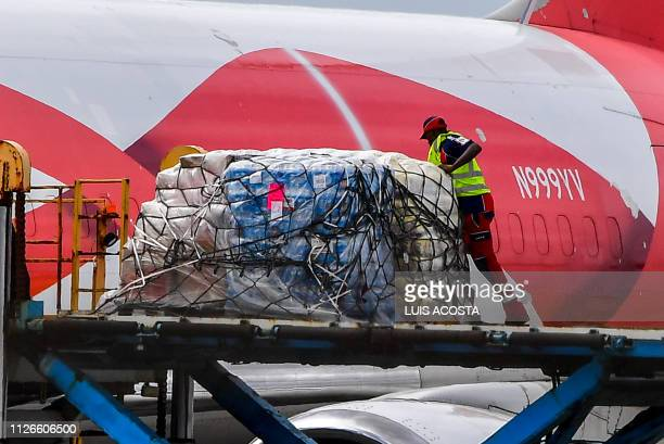 A worker loads food and medicals aid for Venezuela from a US Boeing 767 aircraft shortly after landing at the Hato International Airport in...