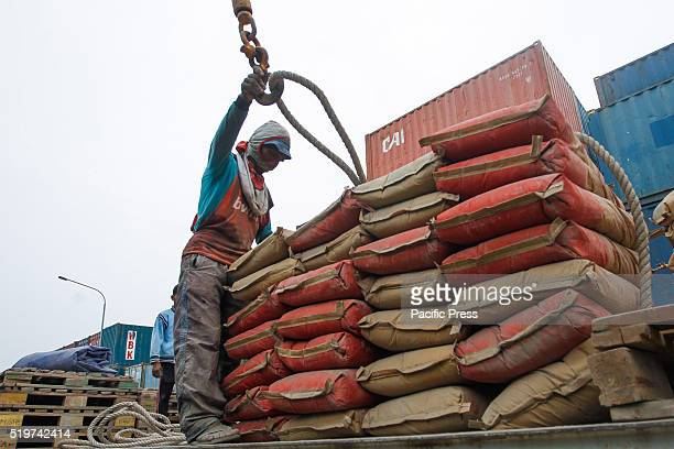 A worker loads sacks of cement on to a ship for transport to Sumatra Island at Sunda Kelapa port