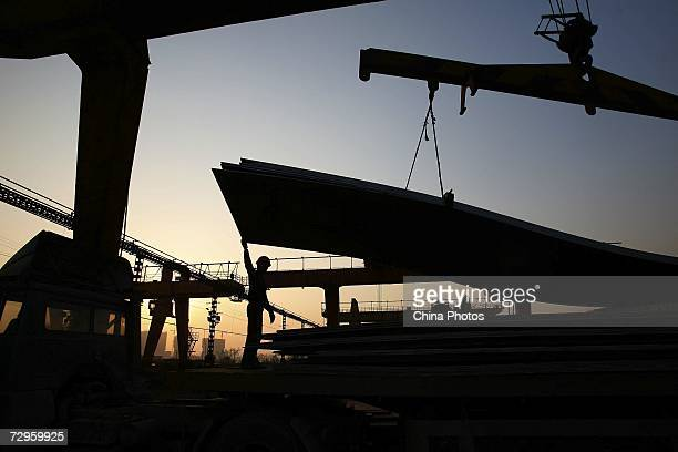 A worker loads steel products from a crane at a factory of Shanghai Baosteel Group on January 9 2007 in Shanghai China Baosteel is China's largest...