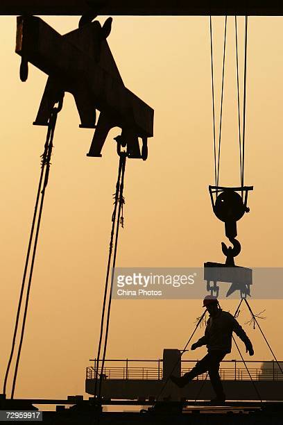 A worker loads steel products on a crane at a factory of Shanghai Baosteel Group on January 9 2007 in Shanghai China Baosteel is China's largest iron...