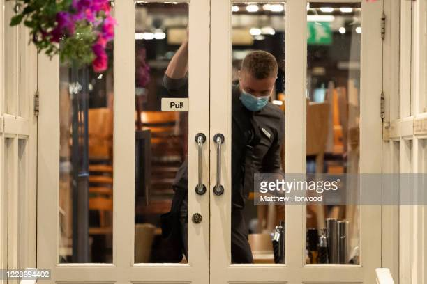 A worker locks the doors of Central Bar on September 24 2020 in Cardiff Wales Pubs cafes and restaurants in Wales will have to shut at 2200 every...