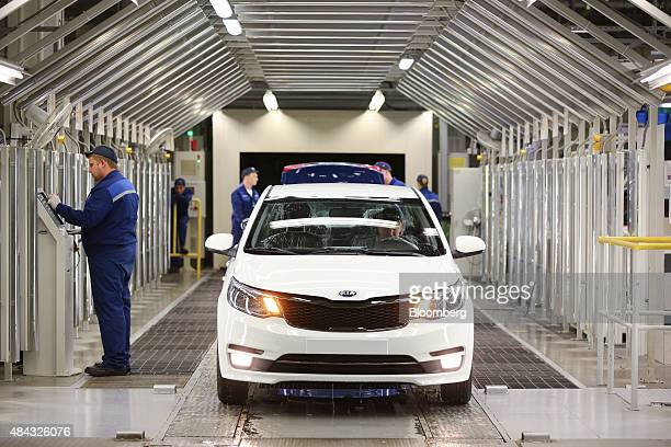 A worker logs details on a computer during a final vehicle quality control inspection of a Kia Rio vehicle on the production line at the Hyundai...