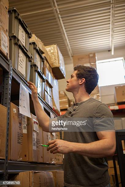 worker looking at cardboard boxes on shelves in warehouse - heshphoto stock pictures, royalty-free photos & images