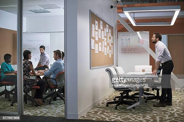 Worker looking at cork board in open-plan office