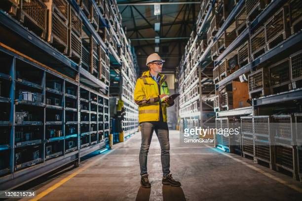 worker looking at crate while holding digital tablet - headwear stock pictures, royalty-free photos & images