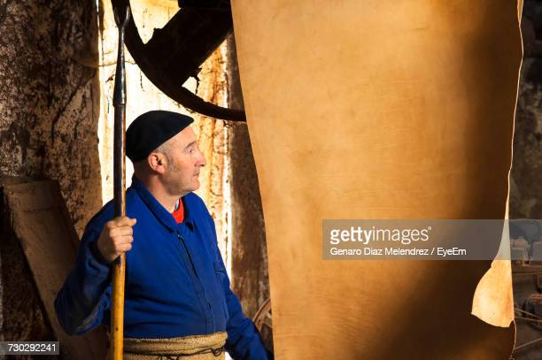 Worker Looking At Leather Hanging In Tannery