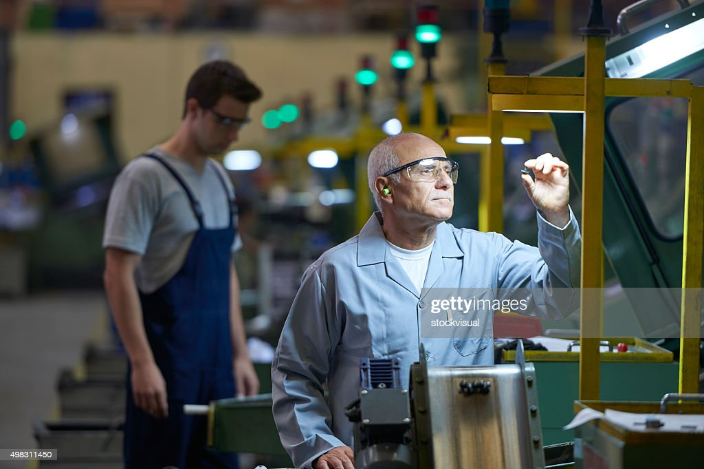 Worker looking at product in bolt factory : Stock Photo