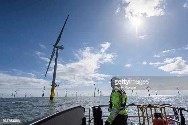 worker looking out from ship to offshore wind farm - wind power stock pictures, royalty-free photos & images