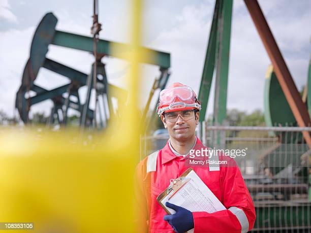 Worker looking to camera, carrying clipboard. In the background are oil pumps above onshore oil wells (nodding donkeys/pumpjacks)