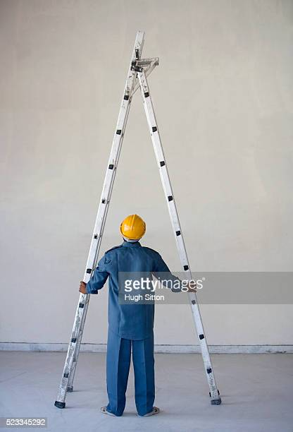 worker looking up at ladder - hugh sitton stock pictures, royalty-free photos & images
