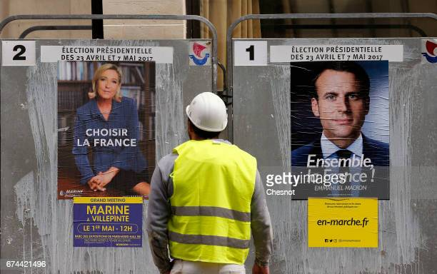 A worker looks at electoral posters of French presidential election candidate for the En Marche movement Emmanuel Macron and French presidential...