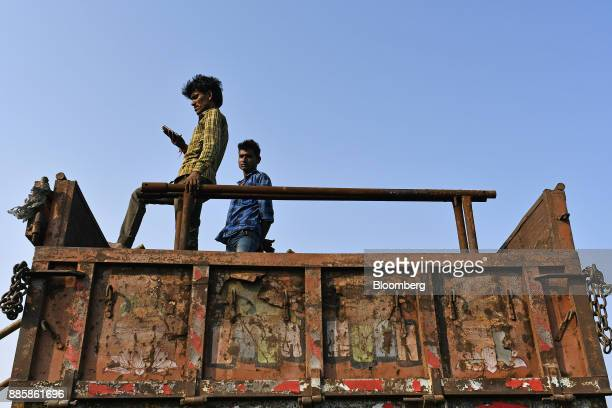 A worker looks at his smartphone while standing on a truck on a project site for a 920squarekilometer industrial area located on the DelhiMumbai...