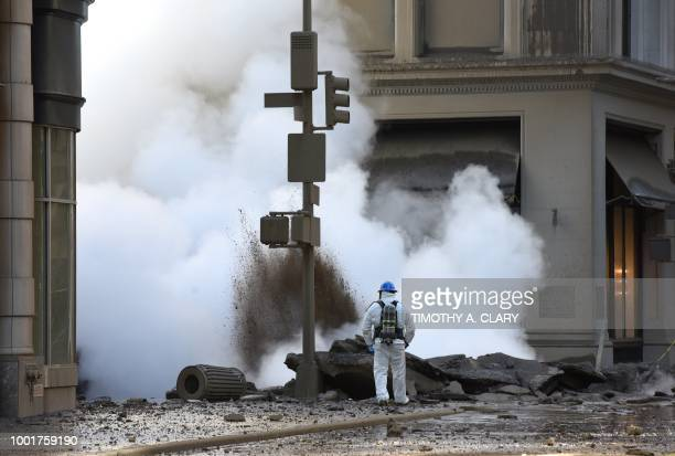 TOPSHOT A worker looks at steam coming from 5th Avenue after a steam explosion tore apart the street in the Flatiron District of New York on July 19...