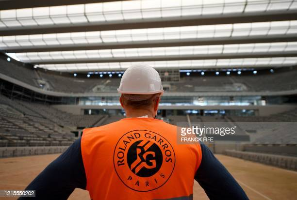 A worker looks at the newly built roof of the Philippe Chatrier central tennis court at the Roland Garros stadium on May 27 in Paris The Roland...