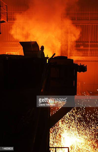 A worker looks down on molten steel being mixed before it is cast into bars called billets at the TAMCO steel mini mill on October 4 2002 in Rancho...