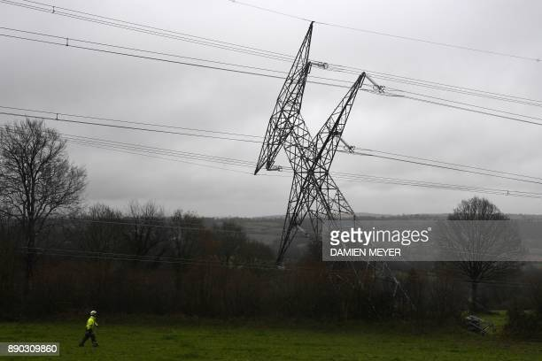 TOPSHOT A worker looks on as a damaged very high voltage electrical pylon lies in a field in Montabot western France on December 11 after an alleged...