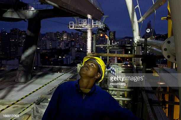 Worker looks on as cable cars are tested at a station in Rio de Janeiro, Brazil, on Tuesday, April 16, 2013. Scheduled to open to the public in April...
