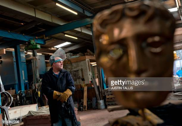 A worker looks on as he prepare molten bronze before casting BAFTA masks during a photo call at the New Pro Foundries west of London on February 7...