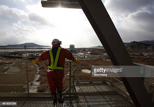 A worker looks out from a tower attached to a conveyor transporting excavated soil for elevating the city's ground level in Rikuzentakata Iwate...