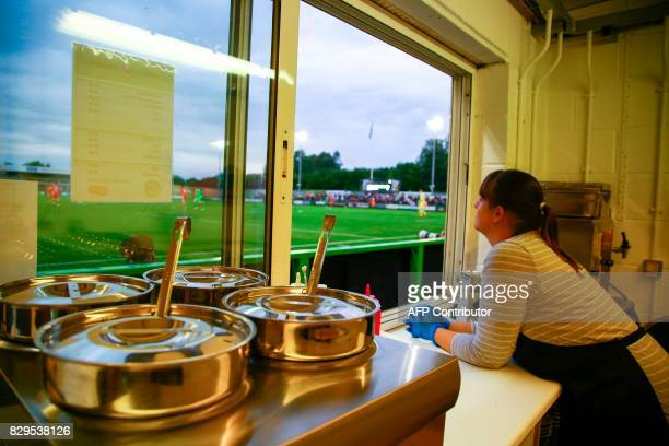 A worker looks put of a serving hatch from the Devil's Kitchen food bar during the EFL Cup football match between Forest Green Rovers and MK Dons at...