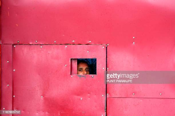TOPSHOT A worker looks through the gate of a closed school in Srinagar on August 19 2019 Some Kashmir schools reopened on August 19 but many pupils...